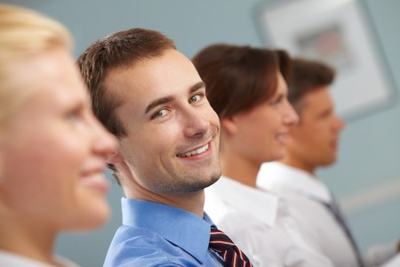 happy people: Image of successful businessman looking at camera among working partners during conference