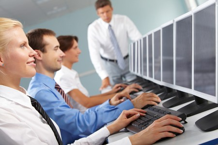 Photo of successful businesspeople typing and looking at monitors in line   photo