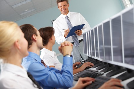 Photo of young businesspeople looking at confident teacher during computer studies   photo