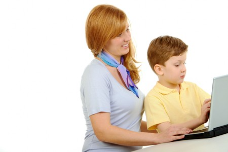 Photo of cute preschooler and his mother looking at laptop monitor while typing photo