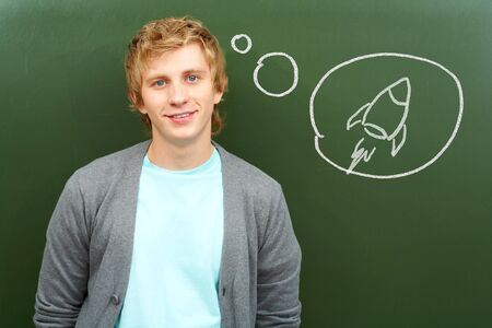 young fellow: Portrait of smart lad by the blackboard thinking of flying on airplane Stock Photo