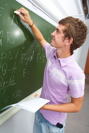Portrait of smart lad by the blackboard writing formulae photo