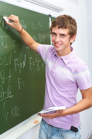 lad: Portrait of smart lad by the blackboard writing formulae