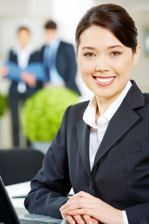 working environment: Portrait of pretty woman looking at camera with smile on the background of working partners
