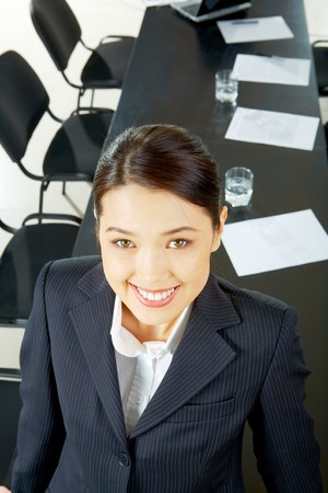 business partner: Portrait of pretty woman looking at camera with smile on the background of long table and chairs Stock Photo