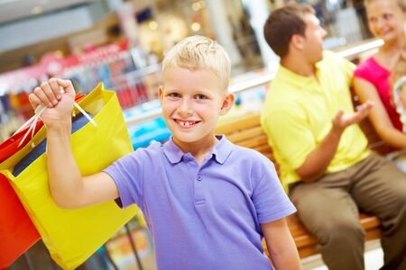 Portrait of happy boy with paperbag looking at camera with his parents behind Stock Photo - 7645902