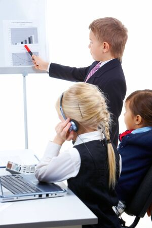 Photo of cute children looking at whiteboard while smart lad presenting project Stock Photo - 7645911
