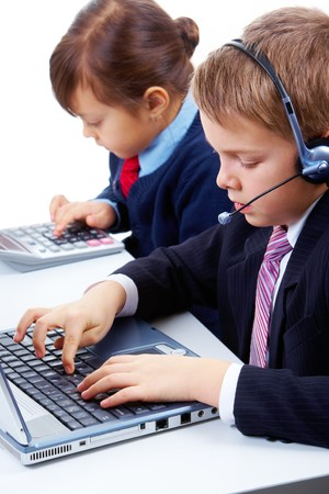 Photo of serious businesschild with headset typing at briefing with cute girl on background photo