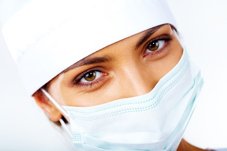 Close-up of medical nurse in mask looking at camera photo