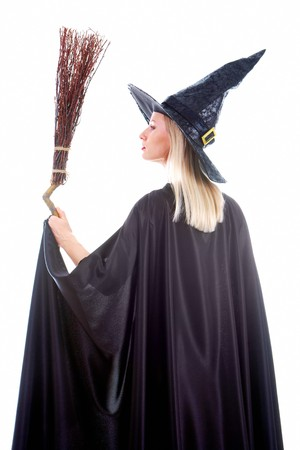 Portrait of young female in black hat and black clothing holding broom photo