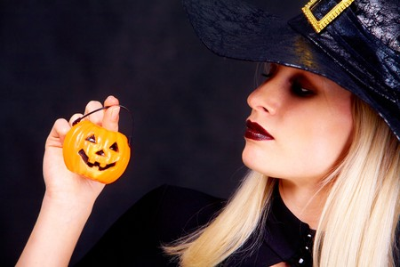 Image of black witch holding pumpkin candle and looking at it photo