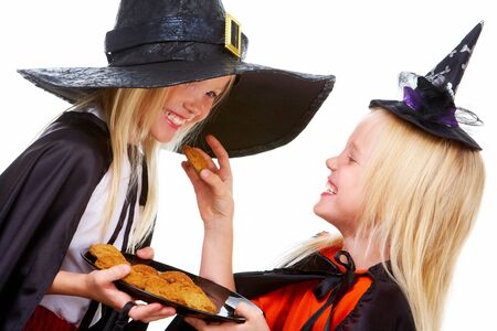 Photo of girl in Halloween costume with tray of bisquits offering one to her twin sister photo