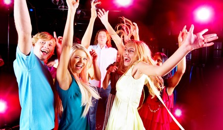 Joyful teens having fun in night club while dancing photo