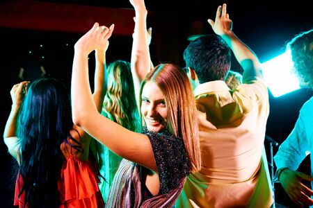 Image of energetic girl looking at camera while dancing on background of her friends Stock Photo - 7695334