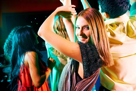 Image of energetic girl looking at camera while dancing on background of her friends Stock Photo - 7695373