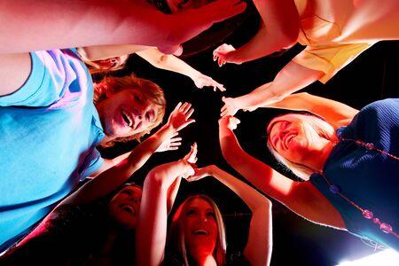 Joyful teens enjoying themselves in night club while dancing photo