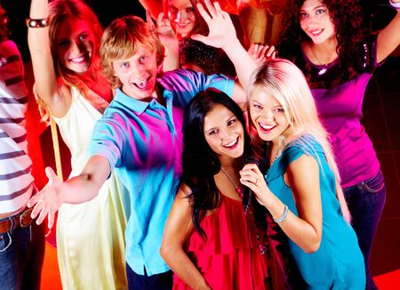 pop singer: Photo of pretty girls singing in mic at party with their friends behind Stock Photo