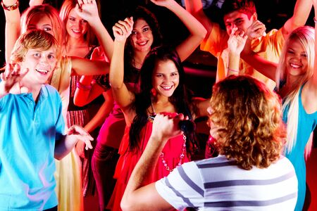 Photo of happy teenage friends looking at guy singing in mic at party Stock Photo - 7695338