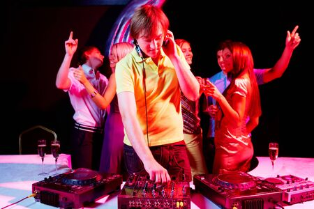 Portrait of handsome deejay working with dancing teens on background photo
