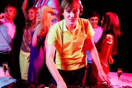 Portrait of handsome deejay looking at camera with dancing teens on background Stock Photo - 7695319
