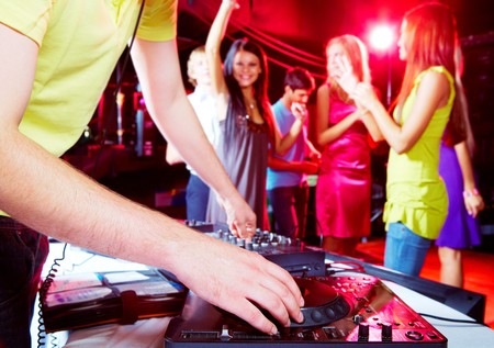 disc jockey: Close-up of human hand spinning turntable with group of dancers on background Stock Photo