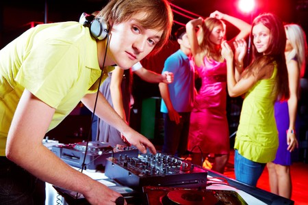 dj boy: Smart deejay looking at camera with dancing teens on background