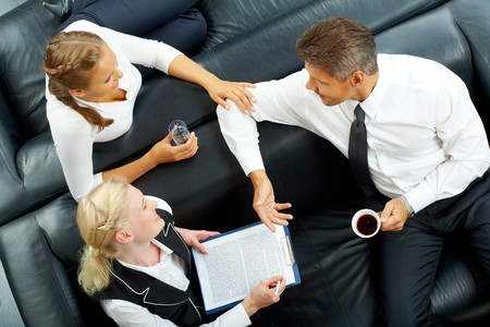 Image of company of successful partners interacting at meeting photo