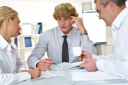 Portrait of three businesspeople discussing plan at meeting  Stock Photo - 7695530