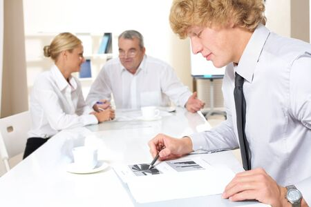 Portrait of confident businessman thinking over business plan with communicating partners at background Stock Photo - 7695514