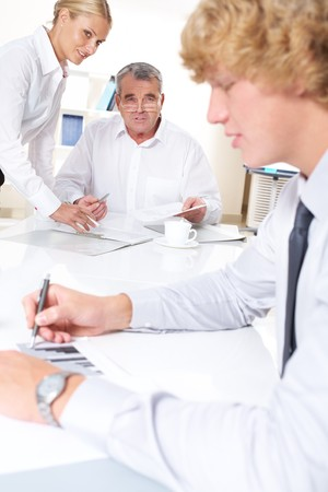 Portrait of confident businessman looking at young worker with friendly secretary near by Stock Photo - 7695471