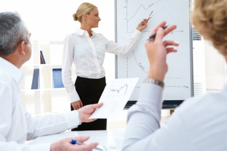 Photo of successful manager standing by whiteboard while her colleagues listening to her photo