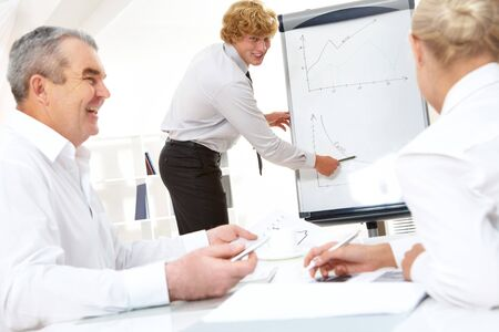 Photo of successful manager standing by whiteboard and explaining his ideas photo