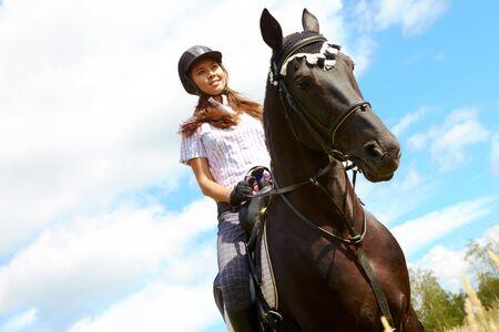 mujer en caballo: Imagen de feliz jockey femenino de caballos de pura raza al aire libre  Foto de archivo