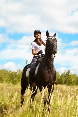 horse riding: Image of happy female jockey sitting on purebred horse outdoors Stock Photo