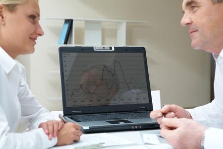 財源: 成功するビジネス パートナーを見てお互いのラップトップと背景の上の肖像画