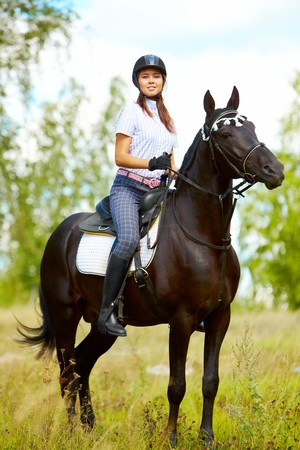 Image of happy female sitting on purebred horse and looking at camera outdoors