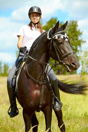 Image of happy female sitting on purebred horse and looking at camera outdoors photo