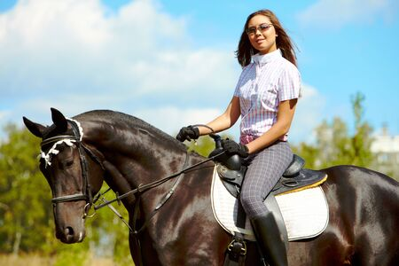 Image of happy female in sunglasses sitting on purebred horse outdoors