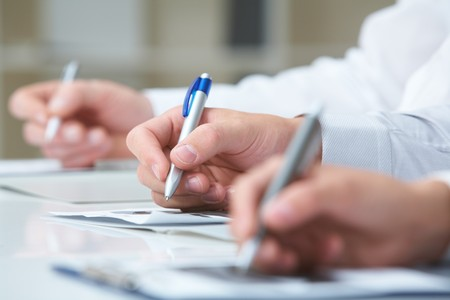 Image of row of people hands writing on papers at seminar Stock Photo - 7695439