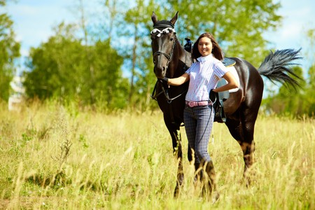 Image of happy female with purebred horse outdoors photo