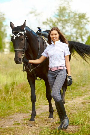 Image of happy female with purebred horse outdoors