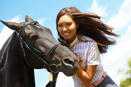 Image of happy female with black purebred horse near by outside photo