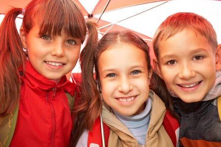Portrait of happy kids looking at camera while under umbrella outside Stock Photo - 7695575