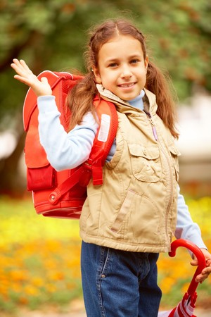 Portrait of happy girl with folded umbrella looking at camera on her way to school photo