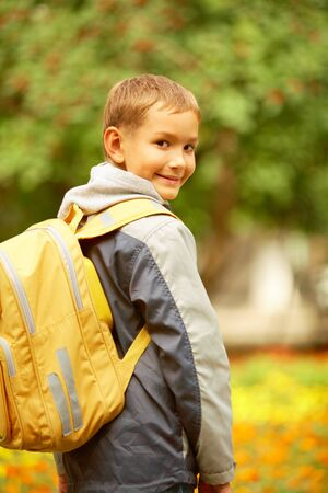 lad: Portrait of happy lad with rucksack on back looking at camera on his way to school