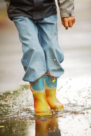 botas de lluvia: Piernas de muchacho feliz corriendo por el Charco y haciendo salpicaduras  Foto de archivo