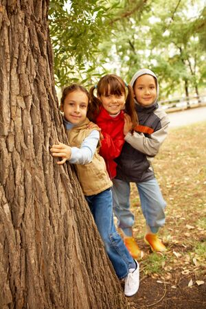 Portrait of happy kids looking at camera while hiding behind tree trunk photo