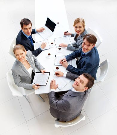 Above view of friendly workteam looking at camera during meeting Stock Photo - 7695505