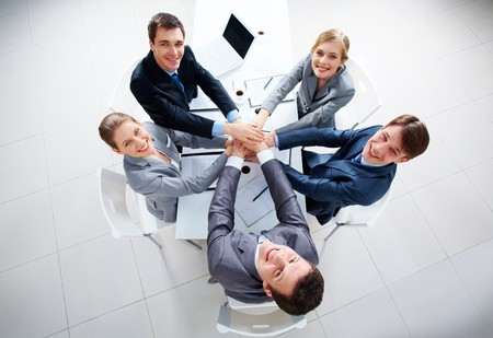 Above view of business people with their hands on top of each other looking at camera Stock Photo - 7695478