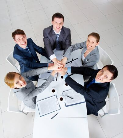 Above view of business people with their hands on top of each other looking at camera Stock Photo - 7695501